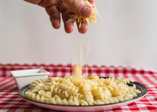 Ręka zraszanie sera na makaron