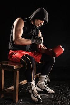 Rękawica sznurowania młodego mężczyzny do kickboxingu
