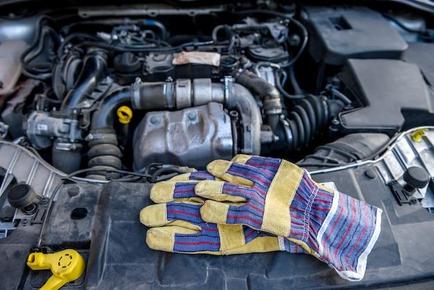 Rękawice ochronne z kluczami przy silniku samochodowym