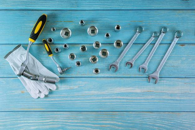 Rękawice robocze w kombinacji kluczy samochodowych klucze do naprawy samochodu auto mechanik drewniany niebieski stół