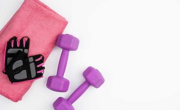 Rękawiczki, para fioletowych hantli i różowy ręcznik na białym tle, widok z góry, miejsce na kopię