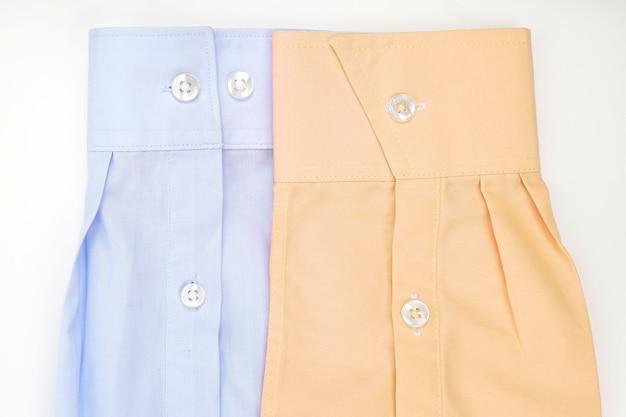 Rękawy z niebiesko-żółtej koszuli na jasnym tle. moda i uroda w ubraniach