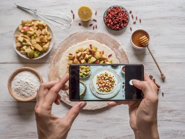 Ręki bierze telefon fotografię jedzenie. szarlotka na święta. ciasto z jagodami goji i jabłkami.