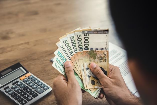 Ręki biznesmen trzyma pieniądze, południowy koren wygrywał banknoty