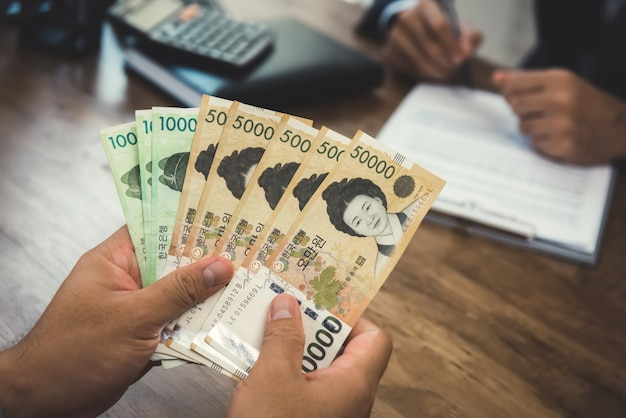 Ręki biznesmena mienia pieniądze, korea południowa wygrywająca waluta, podczas gdy robić kontraktowi z jego partnerem