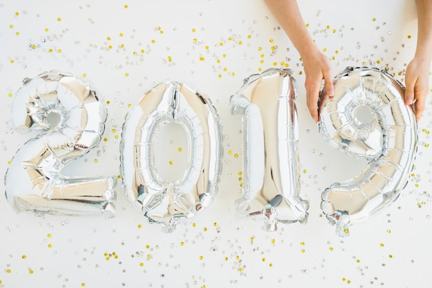 Ręki blisko balonów liczb między confetti