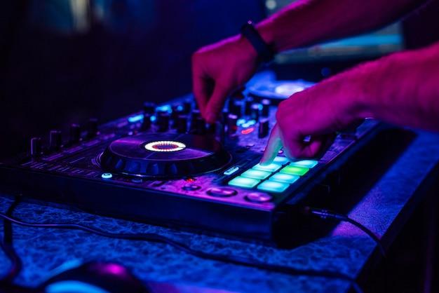 Ręki dj bawić się muzykę na mikserze przy koncertem