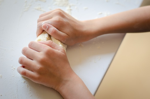 Ręki dzieciak dziewczyna ugniata ciasto na kuchennym kontuarze
