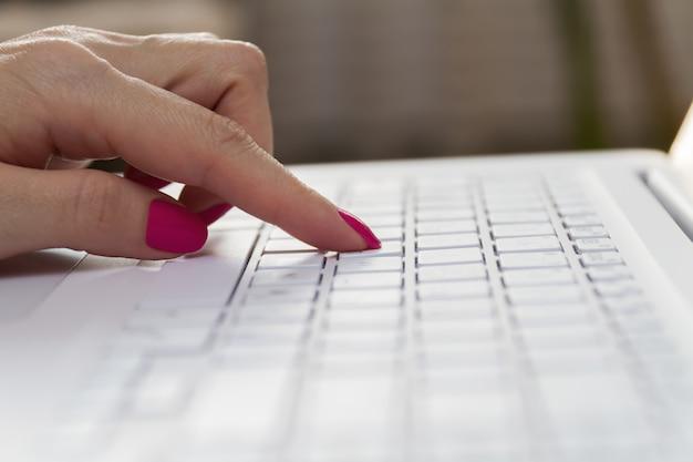 Ręki dziewczyna pisać na maszynie na białej laptop klawiaturze. zbliżenie