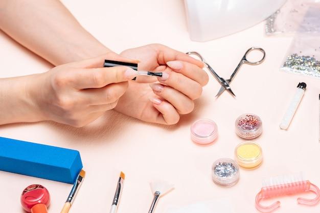 Ręki dziewczyna robi manicure'owi w domu, wręczają zakończenie. widok z góry