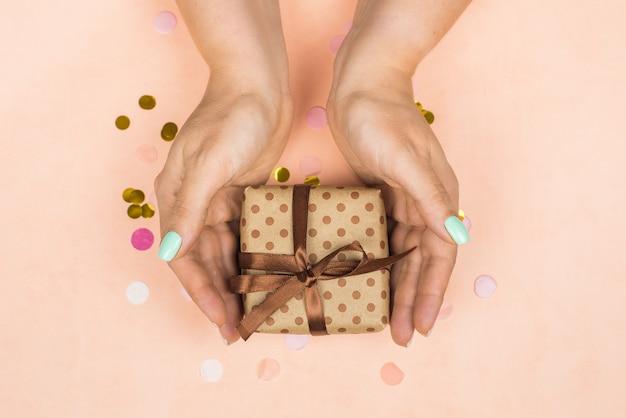 Ręki dziewczyna z błękitnym pastelowym manicure'em trzyma rzemiosło prezent z łękiem na menchiach
