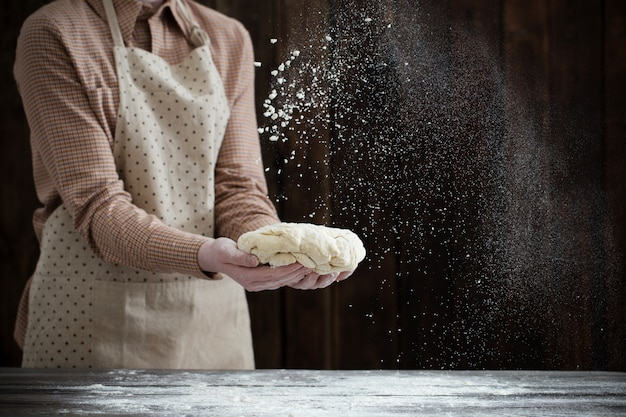 Ręki gotuje ciasto na ciemnym drewnie