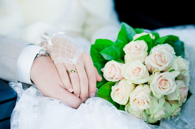 Ręki i pierścionki na ślubnym bukiecie