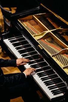 Ręki klasyczny pianista bawić się jego pianino podczas koncerta.