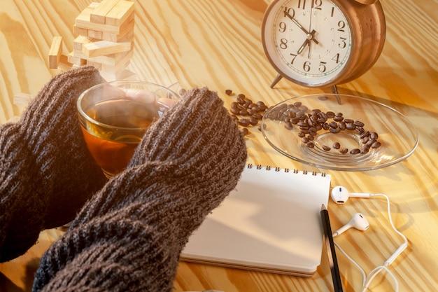 Ręki kobieta trzyma gorącej herbaty w filiżance selekcyjna ostrość.