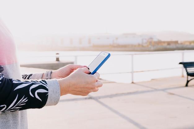 Ręki kobieta trzyma telefonu komórkowego zakończenie up na słonecznym dniu
