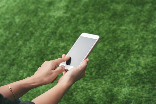 Ręki kobieta używa smartphone plenerowego na trawie