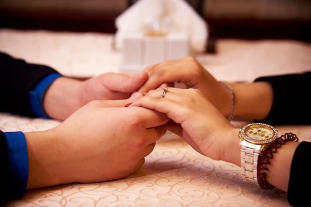 Ręki kochająca para dla stołu w restauracyjnym zakończeniu.