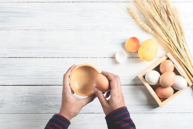 Ręki łama gotowanego jajko z drewnianym pucharem