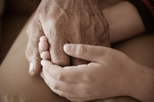 Ręki mały azjatycki dzieciak trzyma biedne starsze dziad mężczyzna ręki