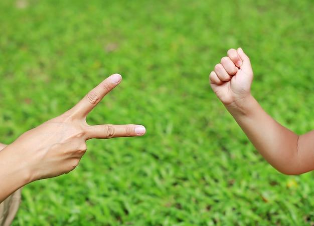 Ręki matka, córka, nożyce i skała, - ręki na zielonej trawy tle