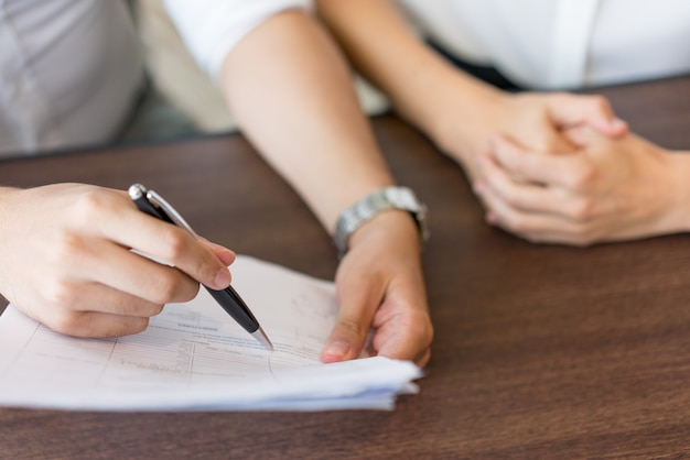 Ręki męski agent wyjaśnia postanowienia kontrakt żeński klient