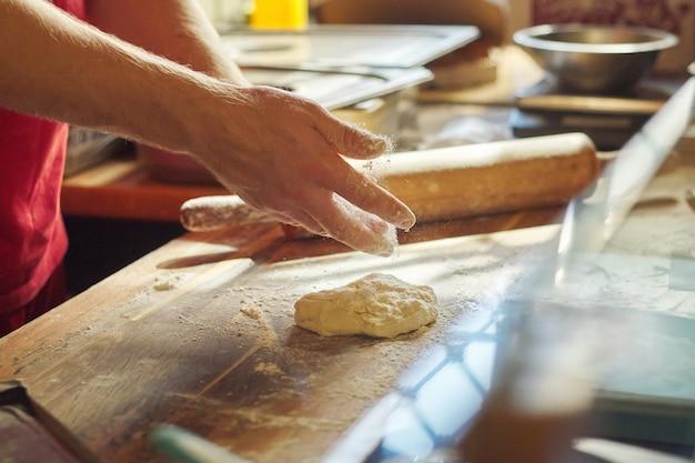 Ręki męski piekarz z mąki ciasta narządzania jedzeniem na drewnianym stole