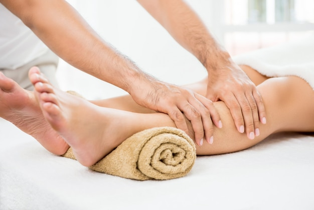 Ręki męski terapeuta daje masażowi kobiety noga