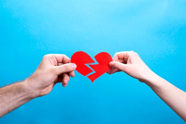 Ręki mężczyzna i kobieta drzeje czerwonego papierowego serce na błękicie