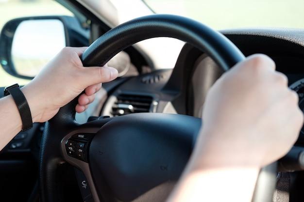 Ręki mężczyzna na kierownicie samochód. mężczyzna jedzie samochodem.