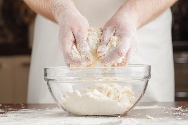 Ręki mężczyzna przygotowywa kopiec chlebowy ciasto na jasnym czerń stole pokrywającym mąką