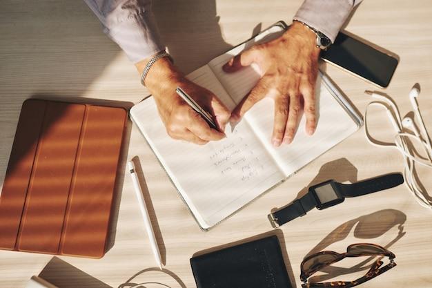 Ręki mężczyzna writing w czasopiśmie i gadżetach na stole