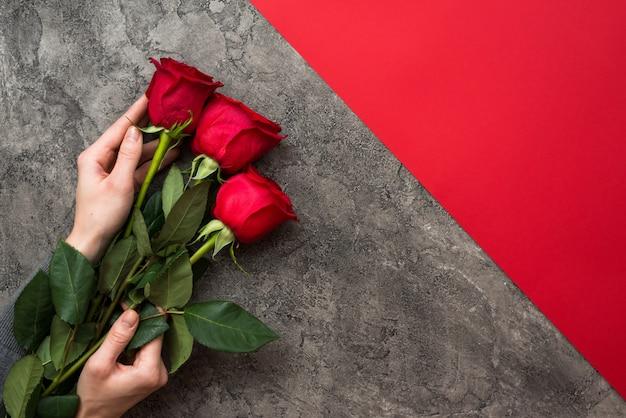 Ręki mienia bukiet czerwone róże odizolowywa na szarość z czerwonym tłem