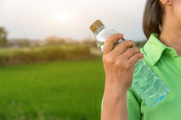Ręki mienia butelki woda z zieleni polem, wakacje letni wakacje plenerowy i widok w wieczór