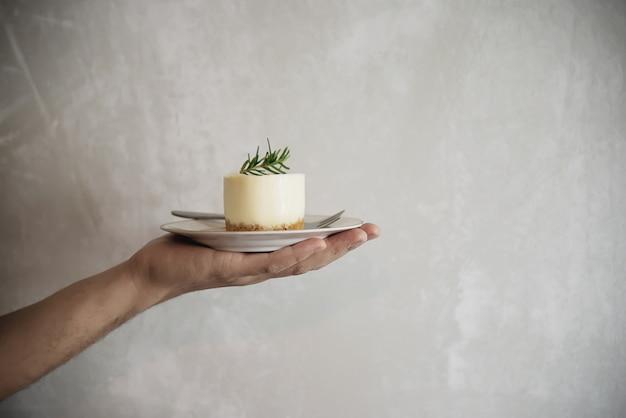 Ręki mienia deser nad taca cementu ściany tłem
