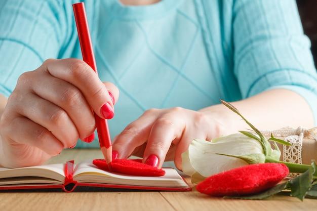 Ręki mienia ołówek na otwartym notatniku i sercach