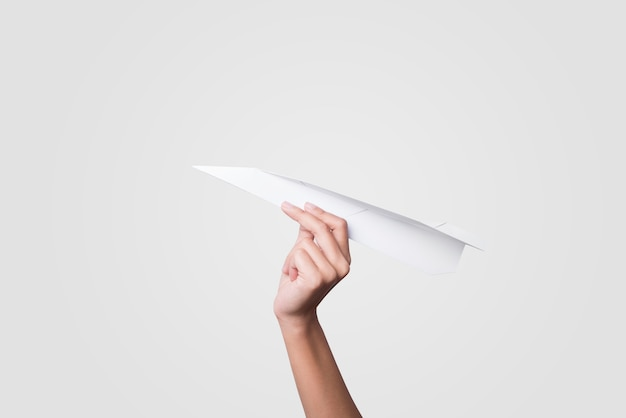 Ręki mienia papieru samolot odizolowywający na popielatym tle.