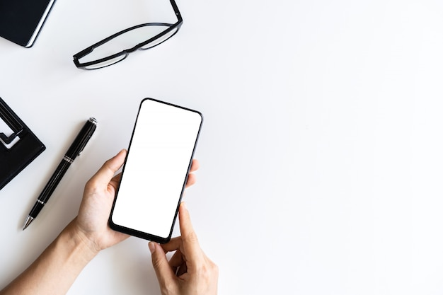 Ręki mienia pusty ekran mądrze telefonu i kartoteki falcówka na biznesowym biurka biurze z kopii przestrzenią, odgórny widok