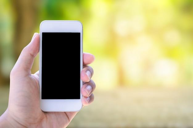 Ręki mienia smartphone na bokeh natury tle