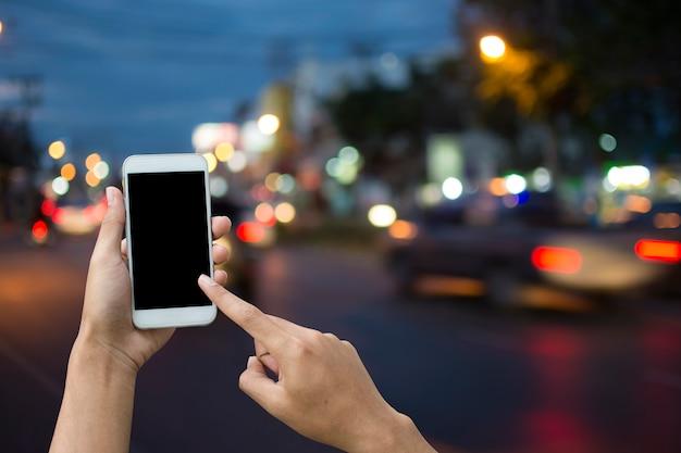 Ręki mienia smartphone na plamy tła transporcie.