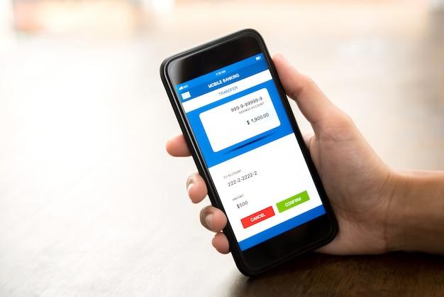 Ręki mienia smartphone pokazuje online elektroniczną bankowość internetowa zastosowanie na ekranie