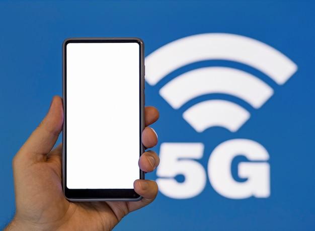 Ręki mienia telefon z 5g symbolu tłem