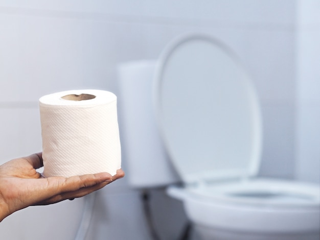 Ręki mienia tkanka nad rozmytą białą toaletą