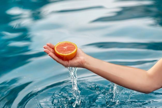 Ręki młoda kobieta trzyma czerwonego grapefruitowego blisko z błękitne wody. zdrowe jedzenie