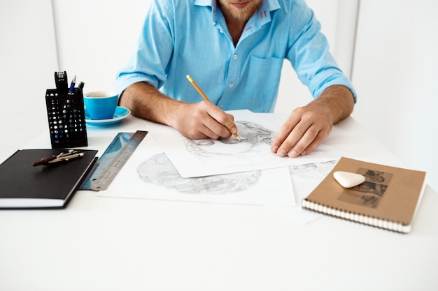 Ręki młody biznesmena obsiadanie przy stołem z ołówkowego rysunku portretem. białe nowoczesne wnętrze biura.