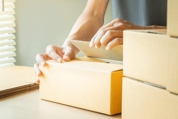 Ręki młody człowiek pakuje pudełka.