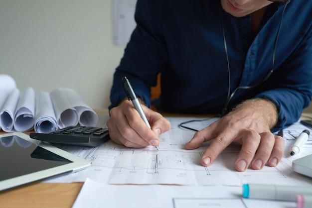 Ręki nie do poznania mężczyzna rysuje na technicznym planie w biurze
