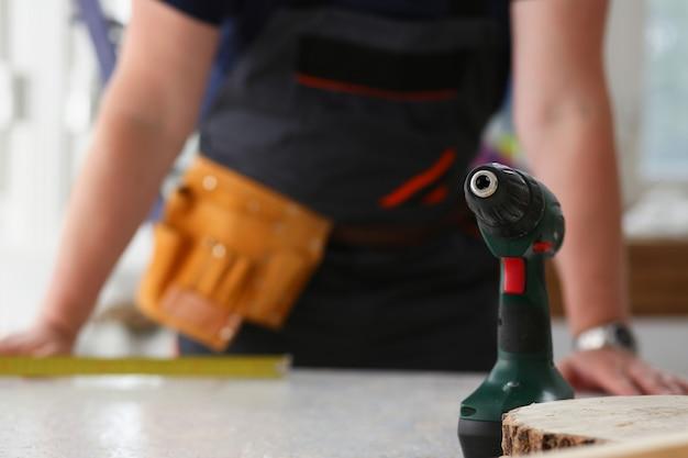 Ręki pracownik używa elektrycznego świderu zbliżenie. ręczna robota diy inspiraci ulepszenia pracy dylemata sklepu żółtego hełma stolarki początkowy pomysł edukaci przemysłowej zawodu kariery pojęcie