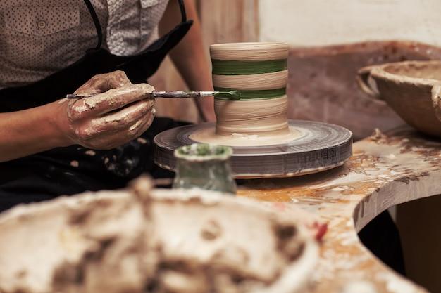 Ręki pracuje rzeźbę z gliną na drewnianym stole w warsztacie i kończy