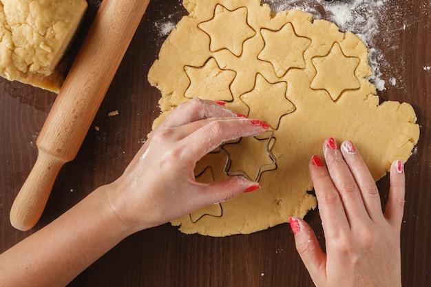 Ręki robi bożych narodzeń ciastkom z metalu obcinaczem